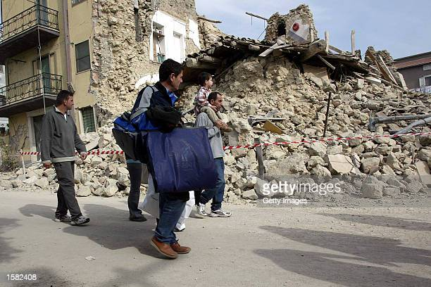 People walk by a home brought down by an earthquake November 1 2002 in San Giuliano di Puglia in south central Italy A series of aftershocks continue...