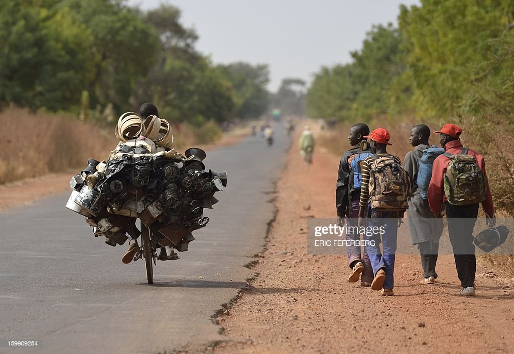 People walk by a man carrying good to sell as he rides a bicyle en route for the market on January 22, 2013 near Segou, 240km North of Bamako. Mali's army chief today said his French-backed forces could reclaim the northern towns of Gao and fabled Timbuktu from Islamists in a month, as the United States began airlifting French troops to Mali.