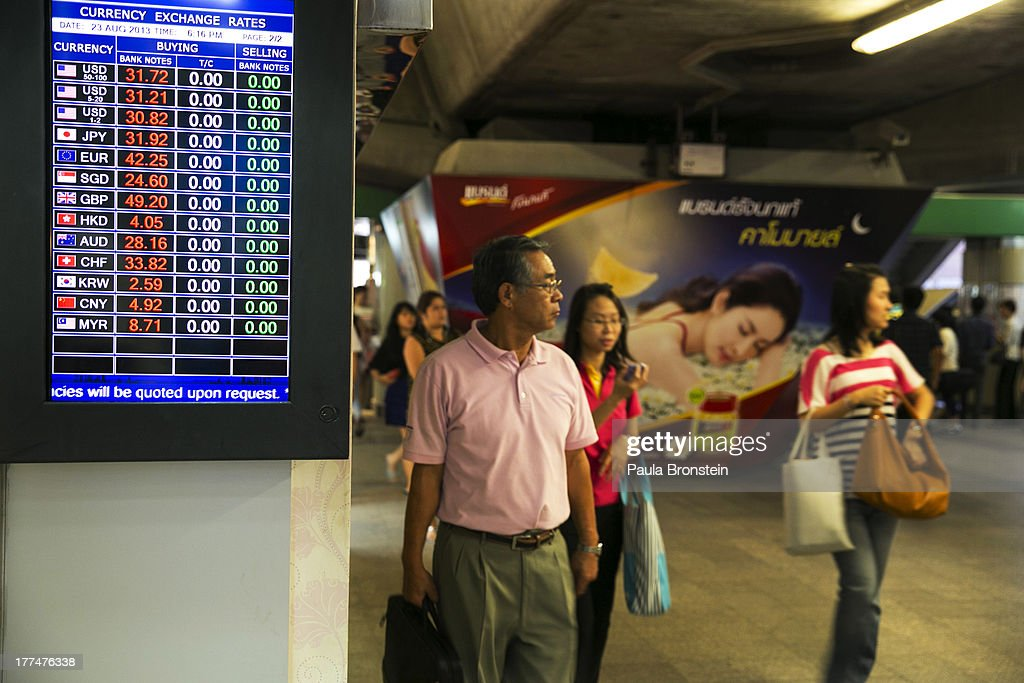 People walk by a money exchange bank kiosk on August 23, 2013 in downtown Bangkok, Thailand. The local currency dropped to its lowest level since August 2010. Against the US dollar the Thai baht fell to 32.09/32.13 dropping about 5% this year.