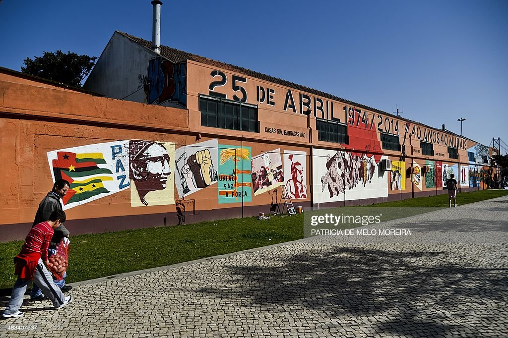 People walk by a mural marking the 40th anniversary of Portugal's Carnations Revolution of April 25 on the walls of a building at Alcantara in Lisbon...