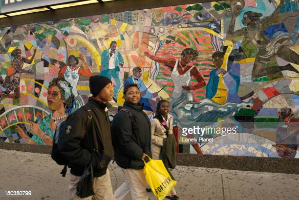 People walk by a mural on 125t Street, Harlem.