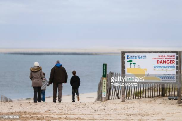 People walk by a placard reading 'dune erosion danger' on Petit Nice beach in La TestedeBuch on March 1 2017 / AFP PHOTO / Thibaud MORITZ