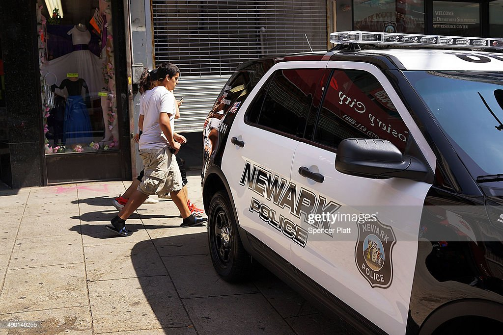 People walk by a police car in downtown on May 13 2014 in Newark New Jersey Voters in New Jersey's largest city go to the polls on May 13 to choose a...