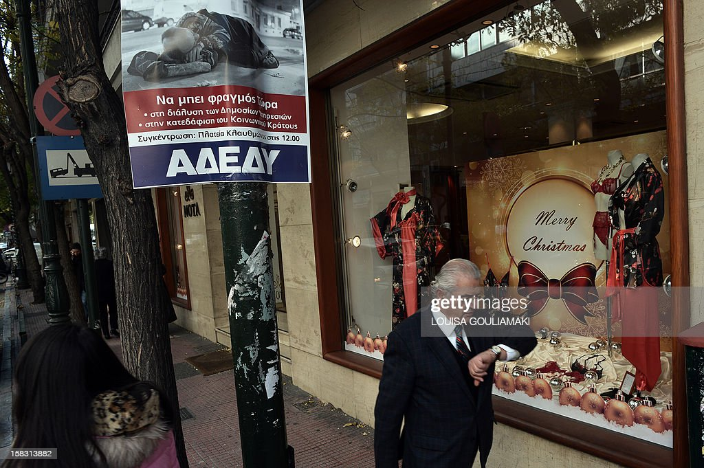 People walk by a private sector union's poster calling for the December 19 strike and featuring a homeless man with a slogan readind 'no to poverty of people' on December 13, 2012 in Athens. Much-needed rescue funds for Athens 'will be flowing to Greece as early as next week,' the head of the Eurogroup Jean-Claude Juncker said on Thursday. AFP PHOTO / LOUISA GOULIAMAKI