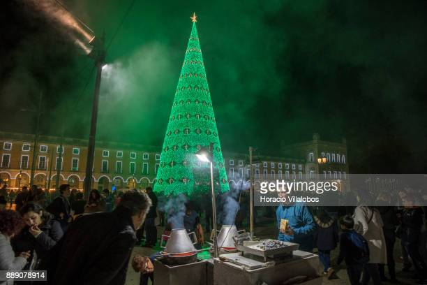 People walk by a roasted chestnuts stall near the large Christmas tree and Christmas and New Year light displays in Praca do Comercio on December 9...
