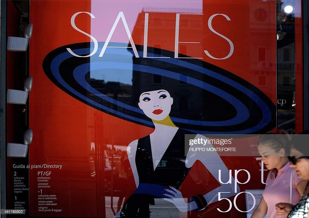 People walk by a shop window advertising sales on July 6, 2014 in downtown Rome, as Italian retailers started their summer sales.