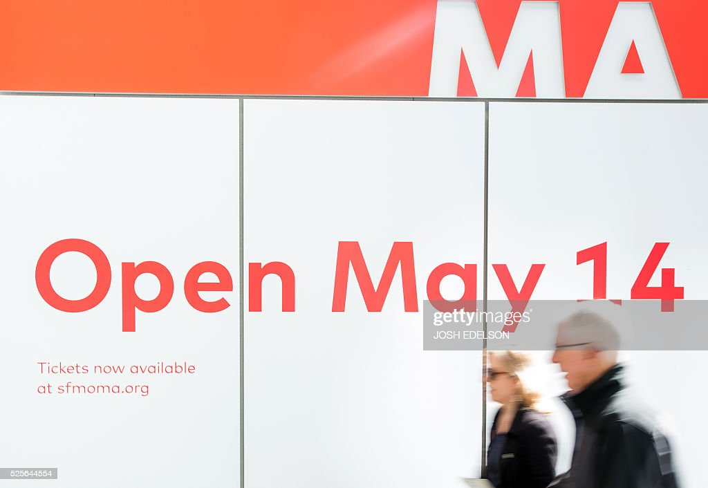 People walk by a sign near the entrance to the San Francisco Museum of Modern Art (SFMOMA) in San Francisco, California on April 28, 2016. The newly redesigned museum integrates a 10-story expansion in a new building and will open to the public on May 14, 2016. / AFP / Josh Edelson