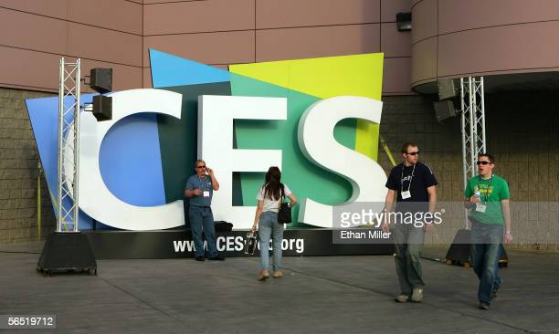 People walk by a sign outside the Las Vegas Convention Center as preparations continue for the International Consumer Electronics Show at the Las...