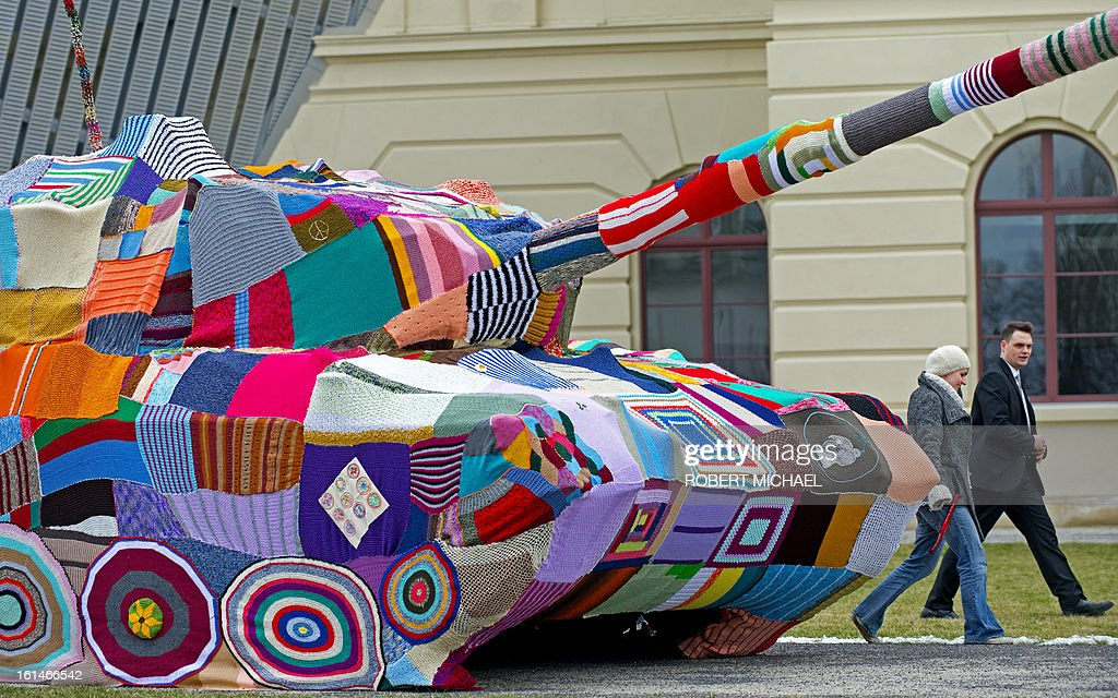People walk by a tank covred by knitted fabric in front of the Museum of Military History in Dresden, eastern Germany, on February 11, 2013. The Leopard I tank takes a stand with a cross-generational handicrafts project against war and violence on the occasion of the 68nd anniversary of the bombing of Dresden.