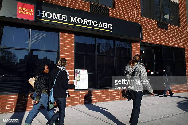 People walk by a Wells Fargo Home Mortgage branch December 3 2008 in the Brooklyn borough of New York City Following the Federal Reserves pledge to...
