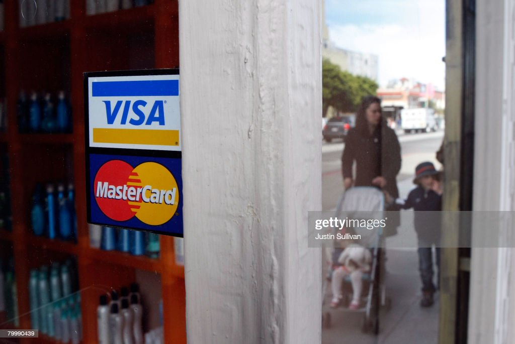 People walk by a window sticker advertising Visa and MasterCard credit cards February 25, 2008 in San Francisco, California. Visa Inc. is hoping that its initial public offering could raise up to $19 billion and becoming the largest IPO in U.S. history.