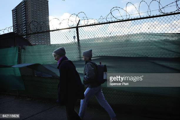 people walk by a work site stands next to the Brooklyn Bridge on February 16 2017 in New York City An annual report by the American Road and...