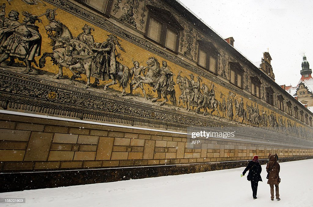 People walk by a102-meter long 'Procession of Princes' wall featuring counts, dukes, princes and kings of the family of the Princely House of Wettin made of 25,000 ceramic tiles on December 11, 2012 in Dresden.