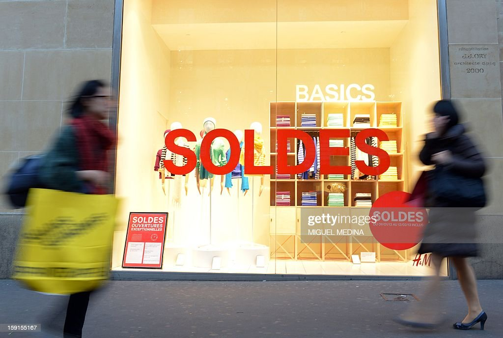 People walk by advertising signs for winter sales in Paris, on January 9, 2013. AFP PHOTO/ MIGUEL MEDINA