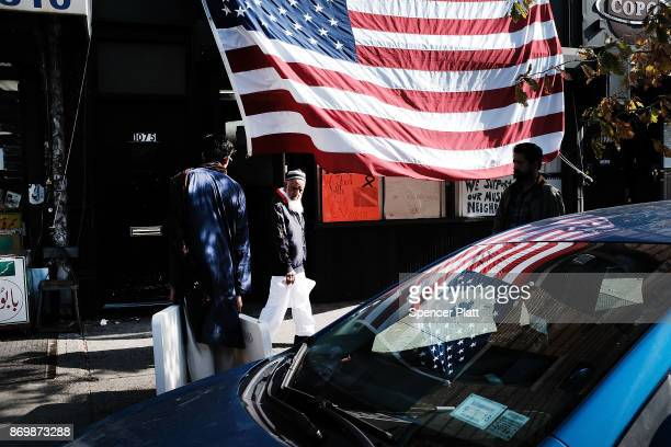 People walk by an American Flag in a Brooklyn community with a large Uzbek community on November 3 2017 in New York City New York City and members of...