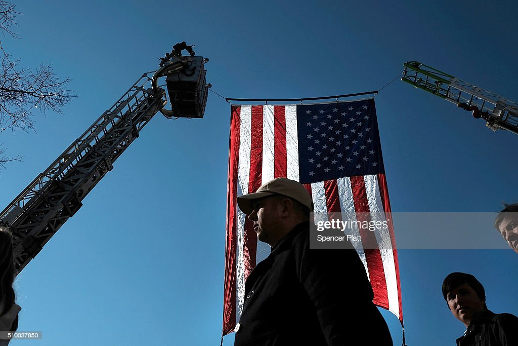 People walk by an American Flag near the site of the Republican Presidential debate on February 13, 2016 in Greenville, South Carolina. This evenings debate will see the six remaining candidates go at each other in a state known to reward more conservative candidates.