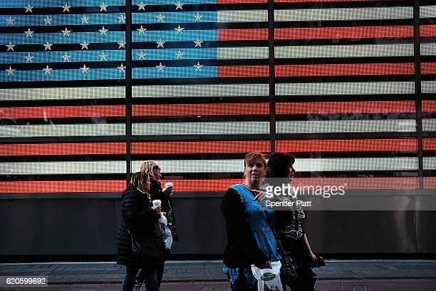 People walk by an American Flag Time Square on November 2 2016 in New York City With the US presidential election only days away many Americans are...