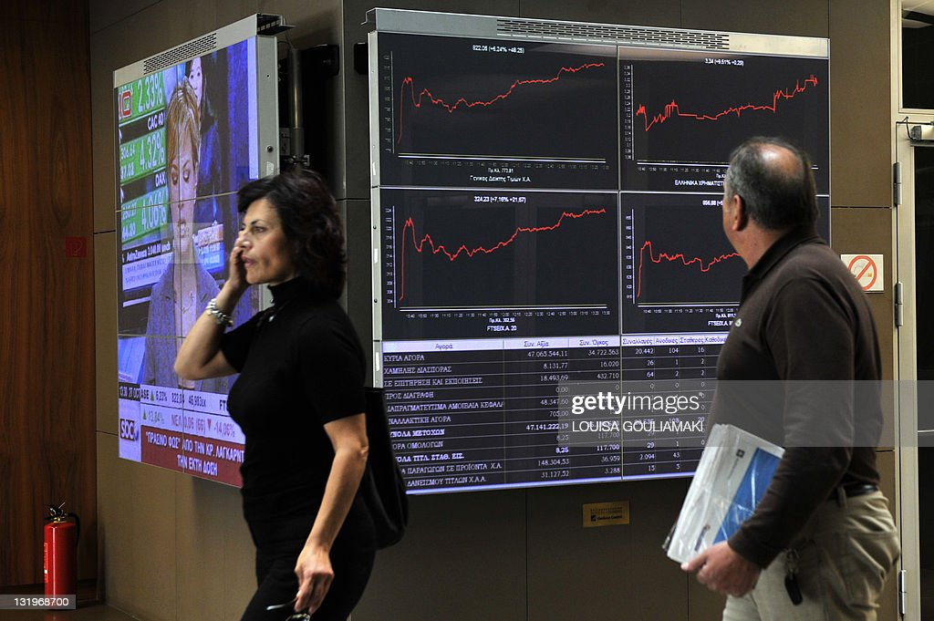 People walk by an electronic display at the Athens stock exchange on October 27 2011 Greece reacted with measured relief on Thursday after European...