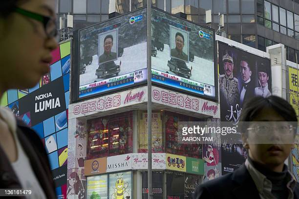 People walk by an electronic display in Hong Kong showing a portrait of North Korea's late leader Kim Jongil placed on top of a car at his funeral in...