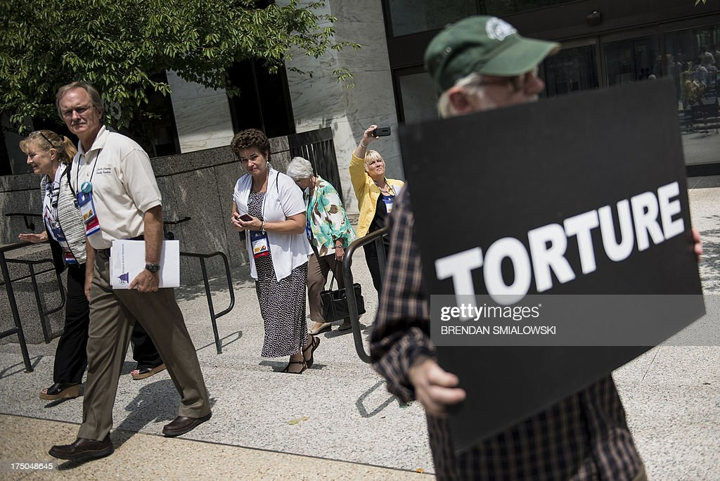 People walk by as activists participate in a mock force feeding while protesting outside the Hart Senate Office Building in Washington, DC July 30, 2013. Activists gathered to protest the use of force feeding prisoners who are held in Guantanamo by the US government. President Barack Obama vowed to close the facility when he first took office in 2009, but four years on the military prison set up in the wake of the September 11, 2001 attacks still holds 166 men. The vast majority of those held at Guantanamo, detained on Afghan battlefields or handed over by other countries, have never been charged or tried, and dozens have been taking part in a hunger strike in recent months. Seventy detainees were taking part in the hunger strike as of July 23, with 46 of them listed as being fed through nasal tubes, according to the military. More than half of the detainees at Guantanamo have been cleared for release and face no charges in the United States. AFP PHOTO/Brendan SMIALOWSKI