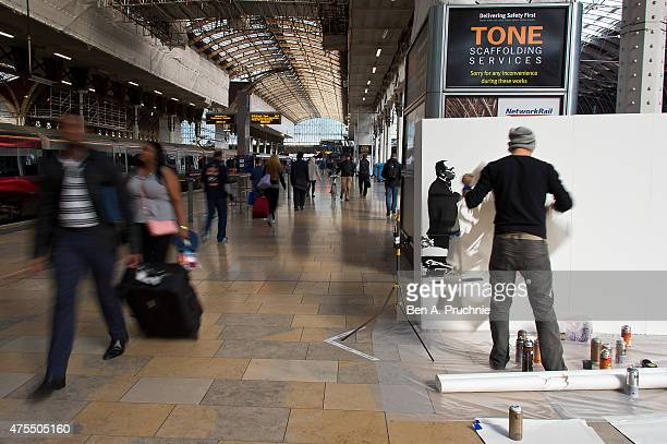 People walk by as Graffiti artist Tom Cat sprays paint creating a dramatic six foot high live art installation Paddington Central to celebrate the...