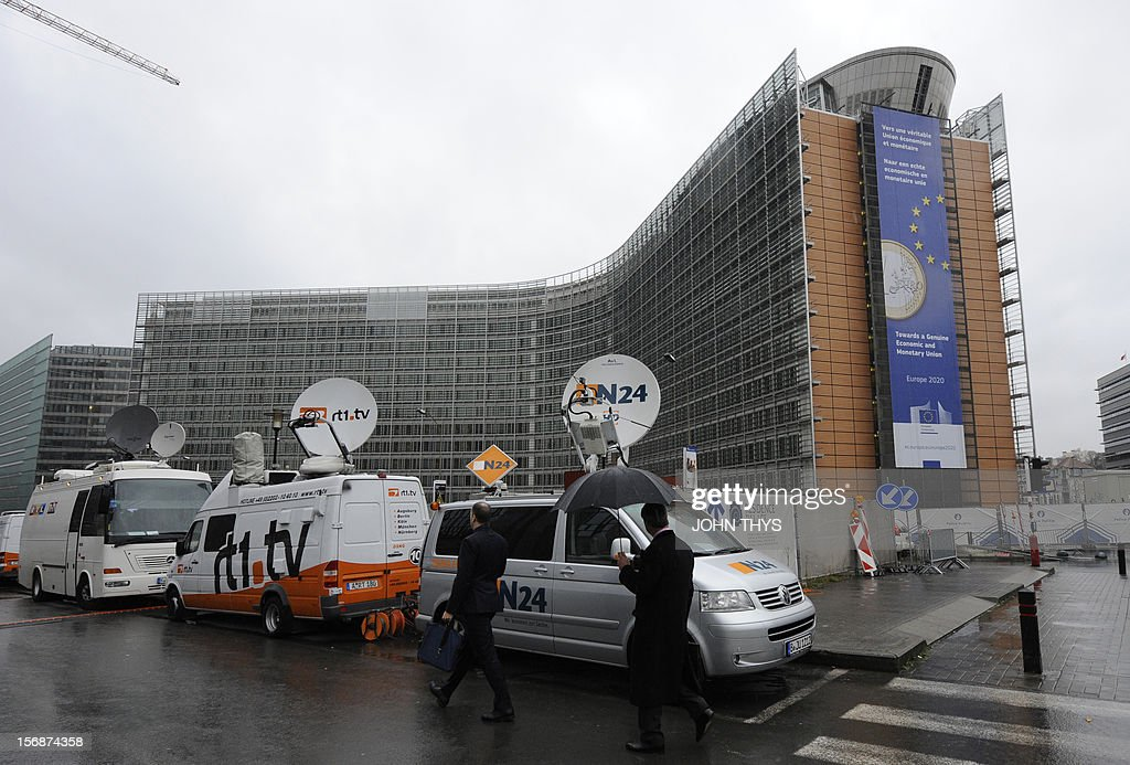 People walk by broadcast trucks parked near the EU Headquarters on November 23, 2012 in Brussels, during a two-day European Union leaders summit called to agree a hotly-contested trillion-euro budget through 2020. European leaders voiced pessimism on reaching a deal on a trillion-euro EU bdget, as gruelling talks pushed into a second day with little prospect of bridging bitter divisions. AFP PHOTO / JOHN THYS