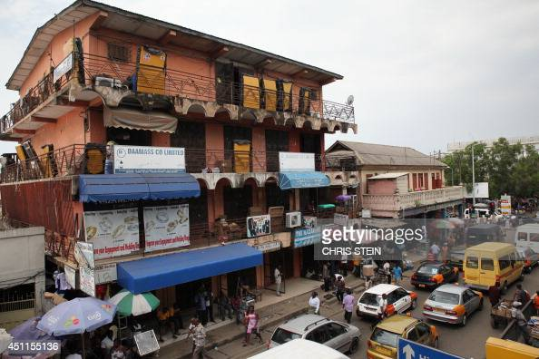 People walk by closed shops on June 24 2014 in Ghana's capital Accra as a major traders' union launched a fourday strike to protest against the...
