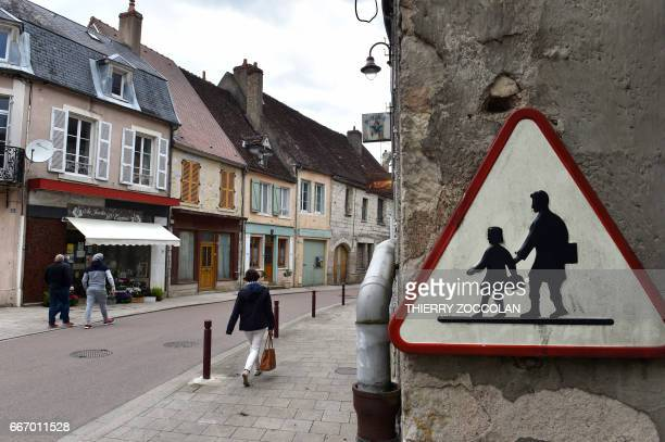 People walk by cosed businesses in Varzy central France on April 4 2017 With its deserted streets 'For Sale' signs and weeds pushing through the...