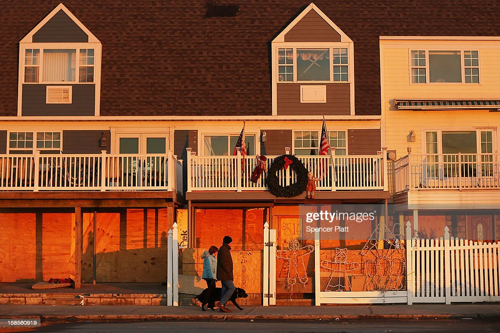 People walk by damaged homes in the heavily damaged Rockaway neighborhood, where a large section of the iconic boardwalk was washed away on November 19, 2012 in the Queens borough of New York City. As the holidays approach after Superstorm Sandy slammed into parts of New York and New Jersey, thousands of residents and businesses are still recovering from the devastation.