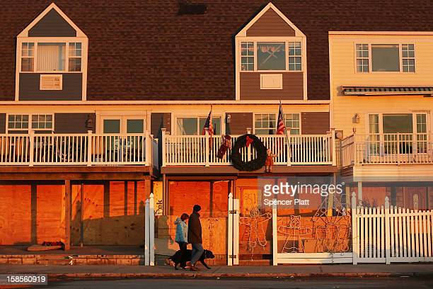 People walk by damaged homes in the heavily damaged Rockaway neighborhood where a large section of the iconic boardwalk was washed away on November...