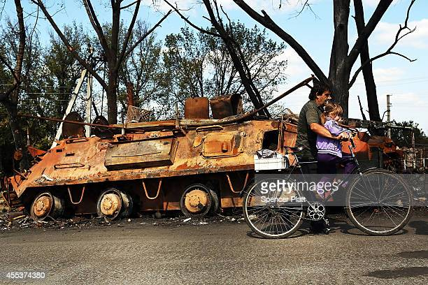 People walk by destroyed military equipment from a recent battle outside of the battered city of Lugansk on September 13 2014 in Lugansk Ukraine...