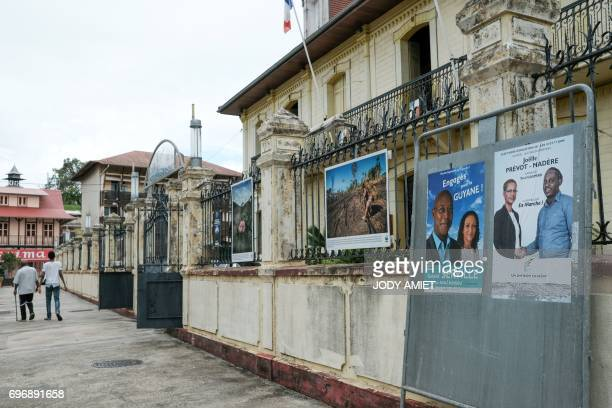 People walk by electoral posters in front of the polling station number 1 in Cayenne on June 17 during the second round of the French legislative...