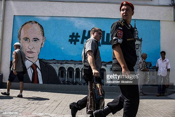 People walk by fresh graffiti depicting Vladimir Putin in Simferopol on August 17 2015 in Simferopol Crimea Russian President Vladimir Putin signed a...