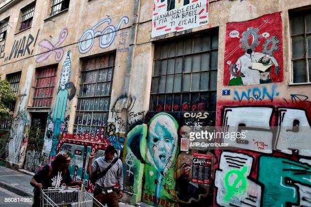 People walk by graffiti by various artists in central Athens on October 11 2017 An ongoing exhibition devoted to 'Artists in Athens City of Crisis'...