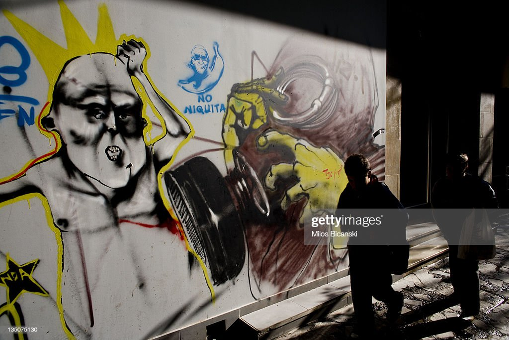 People walk by graffiti displayed on a building on December 6, 2011 in Athens, Greece. Graffiti artists throughout the city are expressing the effects of austerity measures that have plagued the community as Greece continues to struggle in debt while lawmakers today are set to pass next year's budget.