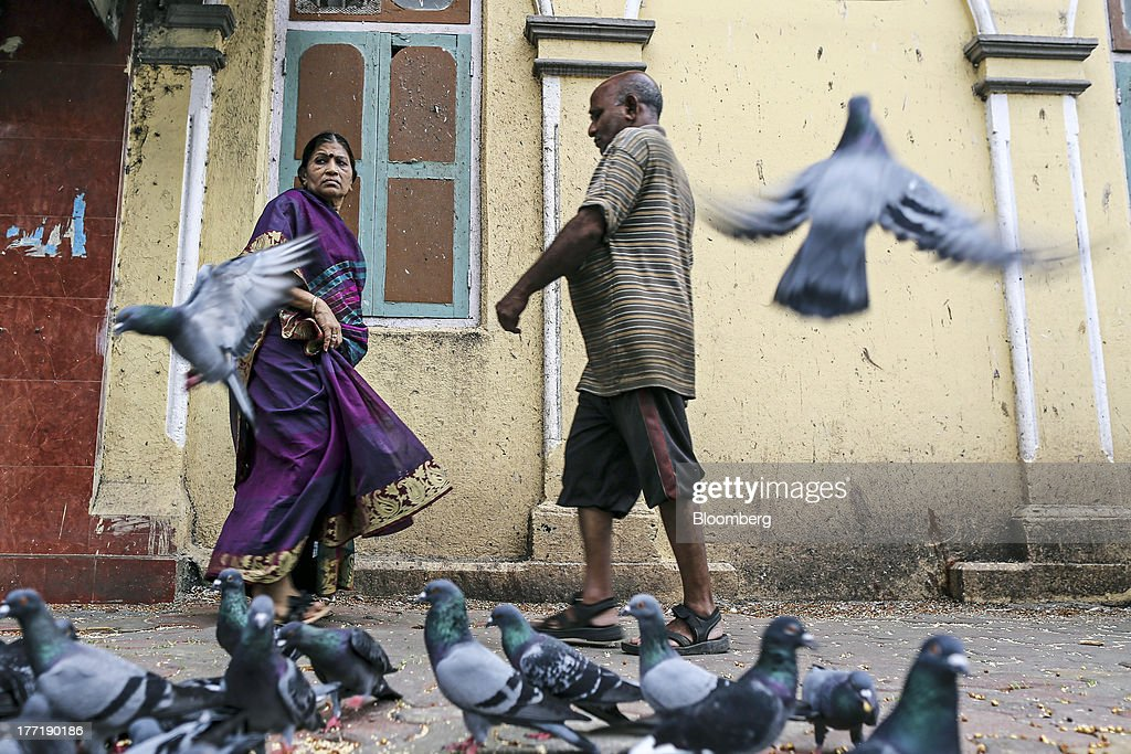 People walk by pigeons outside a temple in Mumbai, India, on Wednesday, Aug. 21, 2013. The prospect of an indecisive 2014 election in India is eroding confidence among global investors that the government can stop the rupees worst drop in more than two decades. Photographer: Dhiraj Singh/Bloomberg via Getty Images
