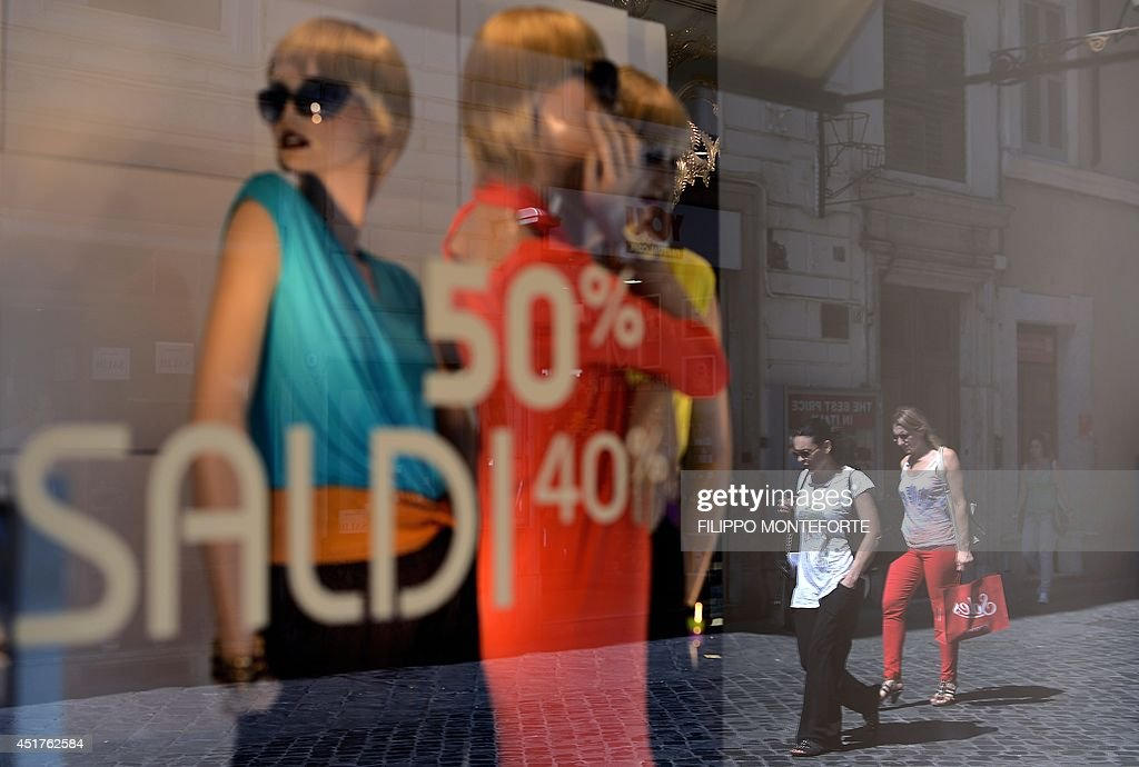 People walk by shop windows advertising sale on July 6, 2014 in downtown Rome, as Italian retailers started their summer sales.