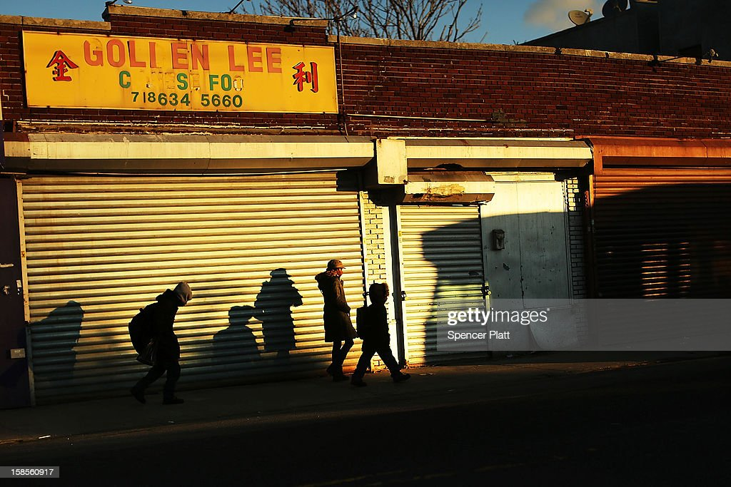 People walk by shuttered businesses in the heavily damaged Rockaway neighborhood, where a large section of the iconic boardwalk was washed away on November 19, 2012 in the Queens borough of New York City. As the holidays approach after Superstorm Sandy slammed into parts of New York and New Jersey, thousands of residents and businesses are still recovering from the devastation.
