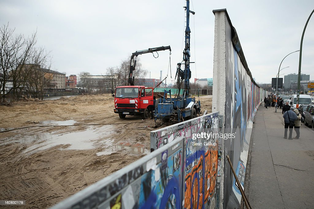 People walk by the construction site next to the East Side Gallery, which is the longest still-standing portion of the former Berlin Wall, where a new hotel is scheduled to be built on February 28, 2013 in Berlin, Germany. According to media reports the developer in charge of the project plans to remove an approximately 25-meter long piece of the Wall and transfer it elsewhere in order to allow access to the construction site. Critics, including East Side Gallery mural artists and Spree River embankment development opponents, decry the move, citing the East Side Gallery's status as a protected landmark and a major tourist attraction.