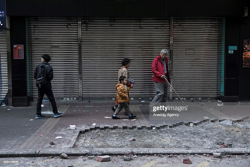 People walk by the debris after the riots occurred in the Mongkok district of Hong Kong on February 9, 2016 in Hong Kong, China. More than 40 police officers and journalists have been injured after a riot with protesters on the first day of Chinese New Year celebrations.