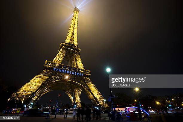 People walk by the Eiffel Tower enlightened with a blue inscription reading '#Human Energy' referring to the largest participatory piece of art...