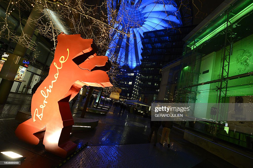 People walk by the giant logo of the Berlinale film festival featuring a bear at the Sony Center on Potsdamer Platz near the Berlinale film festival palace in Berlin, on February 7, 2013. The 63rd Berlin film festival opens with a gala screening of Chinese director Wong Kar Wai's martial arts epic about the mentor of kung fu superstar Bruce Lee.