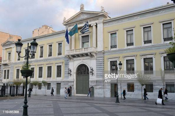 People walk by the headquarters of the National Bank of Greece in Athens on December 10 2009 Greece said its debt had reached a record 300 billion...
