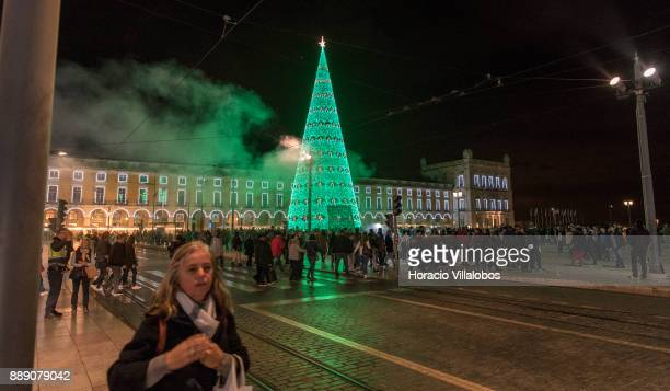 People walk by the large Christmas tree and Christmas and New Year light displays in Praca do Comercio on December 9 2017 in Lisbon Portugal The city...
