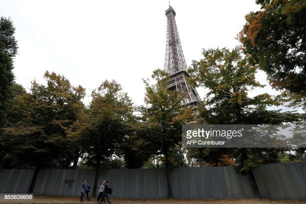 People walk by the metal gates set up for the construction of bulletproof glass walls set to go up around the Eiffel Tower on September 29in Paris A...