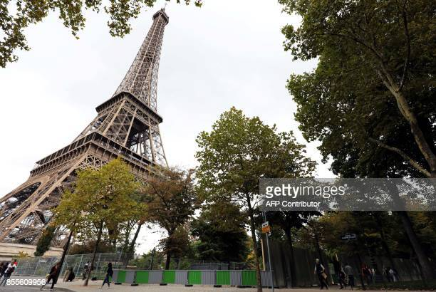 People walk by the metal gates set up for the construction of bulletproof glass walls set to go up around the Eiffel Tower on September 29 in Paris A...