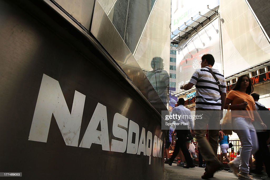 People walk by the Nasdaq stock market one day after the the electronic exchange experienced a a three-hour trading delay due to a technical problem on August 23, 2013 in New York City. Both Wall Street and Nasdaq were operating normally on Friday with stocks up slightly in afternoon trading.