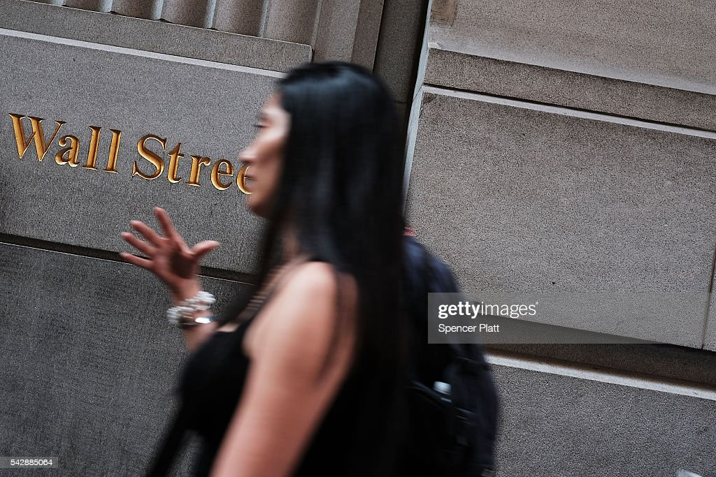 People walk by the New York Stock Exchange (NYSE) on Wall Street following news that the United Kingdom has voted to leave the European Union on June 24, 2016 in New York City. The Dow Jones industrial average closed down over 600 points on the news with markets around the globe pluninging.