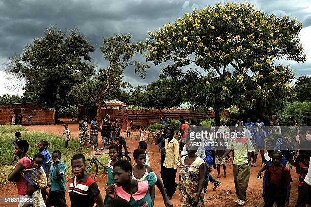 People walk by the road in the outskirts of Lilongwe on March 16 2016 / AFP / ARIS MESSINIS / RESTRICTED TO EDITORIAL USE