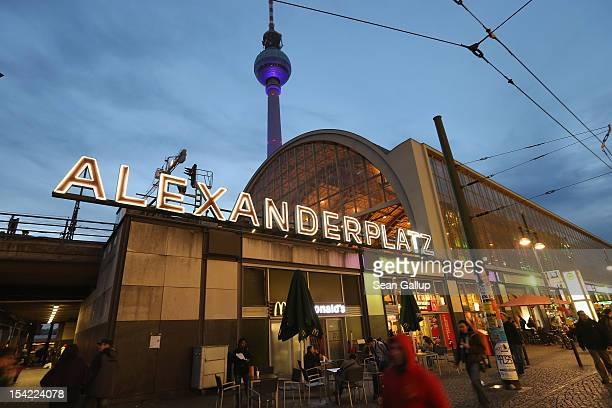 People walk by the SBahn commuter train station at Alexanderplatz as the broadcast tower looms overhead near the site where Jonny was brutally beaten...